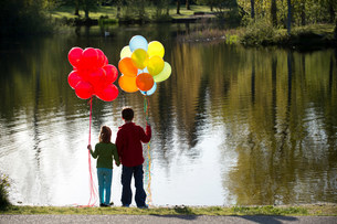Brother and sister in front of lake with bunches of balloonsの写真素材 [FYI03501834]
