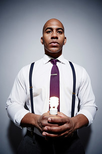 Studio portrait of businessman holding energy saving lightbuの写真素材 [FYI03502005]