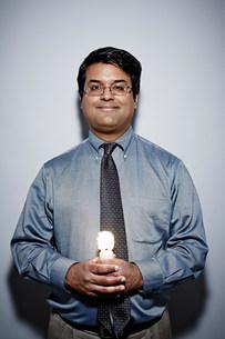 Studio portrait of businessman with energy saving lightbulbの写真素材 [FYI03502006]