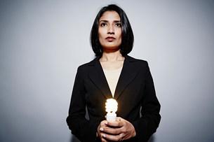 Studio portrait of businesswoman holding energy saving lightの写真素材 [FYI03502013]