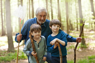 Grandfather and grandsons holding sticks in forest, portraitの写真素材 [FYI03502049]
