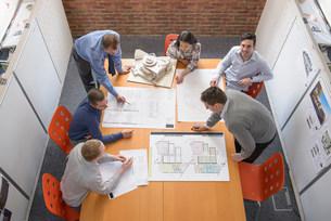 Team of architects discussing plans in meeting roomの写真素材 [FYI03502101]