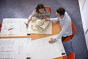 Two architects discussing plans and scale model building inの写真素材 [FYI03502103]