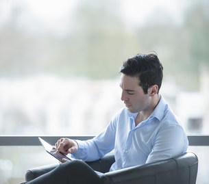 Businessman using digital tablet by window of officeの写真素材 [FYI03502107]