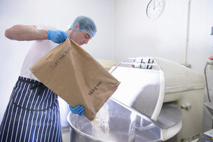 Baker pouring flour from sack into mixerの写真素材 [FYI03502128]