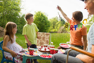 Family with two children celebrating birthday outdoorsの写真素材 [FYI03502341]
