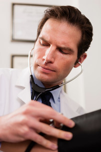 Mid adult doctor using stethoscope and blood pressure cuff oの写真素材 [FYI03502496]