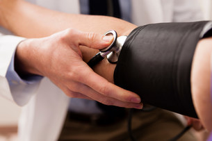 Mid adult doctor using stethoscope and blood pressure cuff oの写真素材 [FYI03502497]