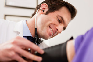 Mid adult doctor using stethoscope and blood pressure cuff oの写真素材 [FYI03502499]