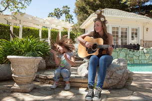 Girl with older sister playing guitarの写真素材 [FYI03502649]