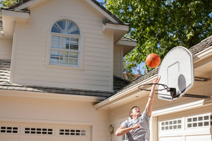 Mature man playing basketball outside garageの写真素材 [FYI03502681]