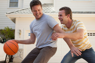 Father and adult son playing basketballの写真素材 [FYI03502682]