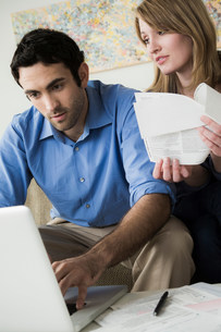 Young couple paying bills onlineの写真素材 [FYI03502764]