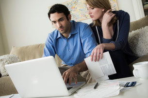 Young couple paying bills onlineの写真素材 [FYI03502766]