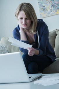Worried young woman holding billsの写真素材 [FYI03502769]