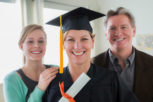 Mother wearing mortarboard with daughter and husbandの写真素材 [FYI03502830]