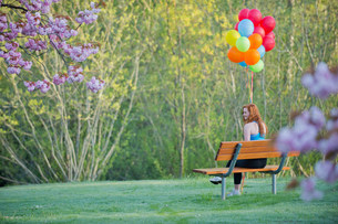 Teenage girl sitting on park bench with balloonsの写真素材 [FYI03502837]