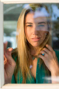 Portrait of young woman looking through window, hand in hairの写真素材 [FYI03502925]
