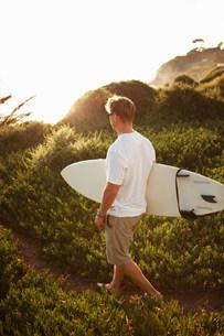 Surfer walking on pathwayの写真素材 [FYI03503342]