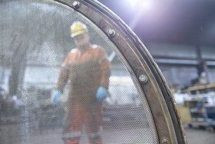 Portrait of worker behind industrial sieve in steel foundryの写真素材 [FYI03503504]