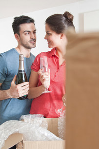 Young couple celebrating with champagne amongst cardboard boの写真素材 [FYI03503545]