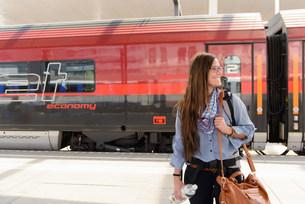 Female backpacker arriving in train station, Salzburg, Austrの写真素材 [FYI03503737]