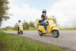Couple on scooters riding down rural roadの写真素材 [FYI03503844]