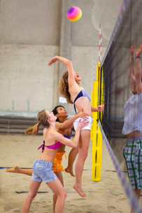 Friends playing beach volleyball at sports centreの写真素材 [FYI03503904]