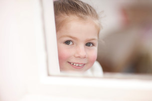 Close up of young girl looking through window at ballet clasの写真素材 [FYI03504026]