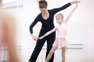 Young ballerina practicing pose with teacherの写真素材 [FYI03504033]