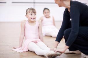 Teacher adjusting feet position of young ballerinaの写真素材 [FYI03504044]