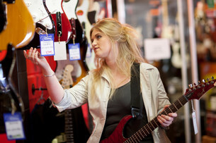 Young women looking at guitars in music storeの写真素材 [FYI03504167]