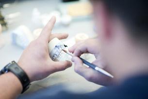 Dental technician repairing dentures in labの写真素材 [FYI03504194]