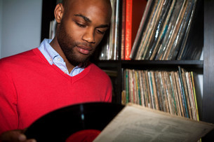 Portrait of young man removing vinyl record from sleeveの写真素材 [FYI03504356]