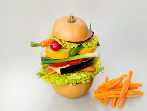 Healthy diet illustrated by a raw vegetarian burger and carrの写真素材 [FYI03504396]