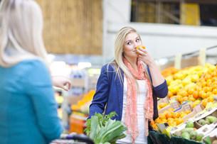 Young women buying produce in indoor marketの写真素材 [FYI03504423]