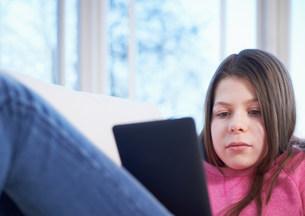 Girl using digital tablet on sofaの写真素材 [FYI03504683]