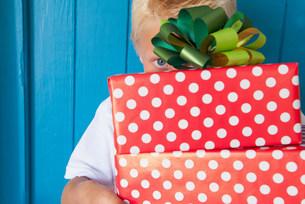 Boy peeping behind gifts in handの写真素材 [FYI03504817]