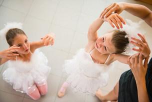 Mature ballet teacher arranging ballerina's handsの写真素材 [FYI03504833]
