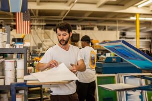 Worker picking up paper in screen print workshopの写真素材 [FYI03504866]