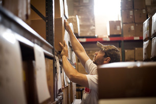 Worker reaching up for cardboard box stored in warehouseの写真素材 [FYI03504889]