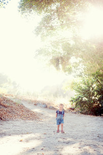 Young female toddler with hands in pockets on dirt trackの写真素材 [FYI03505170]
