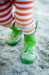 Legs of young male toddler wearing smiley wellington bootsの写真素材 [FYI03505173]