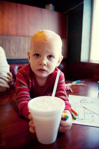 Young boy reaching for milkshake in cafeの写真素材 [FYI03505238]
