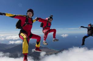 Small group of skydivers reaching to join handsの写真素材 [FYI03505270]