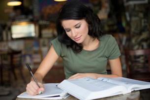 Portrait of teenage girl studying in coffee houseの写真素材 [FYI03505388]