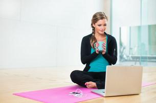 Young woman on yoga mat with mug of teaの写真素材 [FYI03505508]