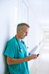 Surgeon standing in corridor looking at smartphoneの写真素材 [FYI03505628]