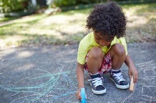 Boy drawing with chalk on sidewalkの写真素材 [FYI03506119]