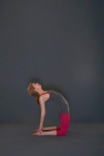 Woman in yoga pose on grey backgroundの写真素材 [FYI03506244]